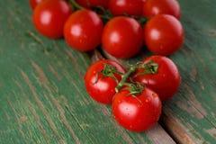 Tomates juteuses mûres humides sur la table verte Photos libres de droits