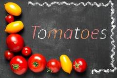 Tomates juteuses sur le tableau noir Images stock