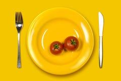 Tomates mûres dans la plaque jaune Photographie stock libre de droits
