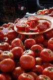 Tomates mûres, juteuses, rouges d'un plat pour examiner par des acheteurs sur le marché végétal photographie stock libre de droits