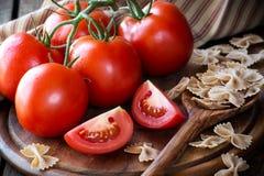 Tomates mûres rouges fraîches avec les pâtes complètes crues de noeud papillon Photos libres de droits