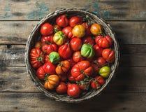 Tomates mûres colorées fraîches d'héritage dans le panier au-dessus du fond en bois Image libre de droits
