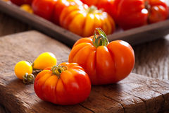 Tomates mûres de boeuf sur la planche à découper Photo libre de droits