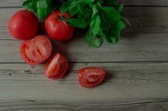 Tomates mûres et herbes fraîches Photographie stock libre de droits