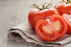 Tomates mûres fraîches avec des halfs sur la table en bois Photo libre de droits