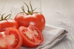 Tomates mûres fraîches avec des halfs sur la table en bois Photos stock
