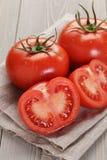 Tomates mûres fraîches avec des halfs sur la table en bois Photographie stock