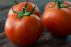 Tomates mûres juteuses sur une table en bois Images stock