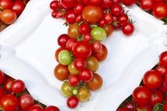 Tomates mûres rouges d'un plat blanc Photographie stock libre de droits