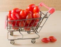 Tomates maduros de la uva en el pequeño carro de la compra Imágenes de archivo libres de regalías