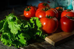 Tomates maduros em uma placa de corte Fotografia de Stock