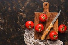 Tomates maduros em uma placa de corte com uma faca e um guardanapo Vista superior, espaço para o texto imagens de stock royalty free