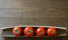 Tomates maduros en el fondo de madera Fotos de archivo