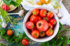 Tomates maduros en una placa en una tabla de madera Fotografía de archivo