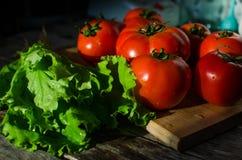 Tomates maduros en una tabla de cortar Fotografía de archivo