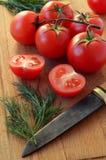 Tomates maduros, inteiro e cortado com a faca na BO de corte de madeira Fotos de Stock Royalty Free