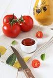 Tomates maduros, jarro de cerámica y salsa de tomate de tomate Foto de archivo