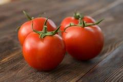 Tomates maduros jugosos en una tabla de madera Foto de archivo libre de regalías