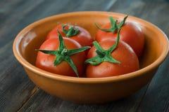 Tomates maduros jugosos en una tabla de madera Imagen de archivo libre de regalías