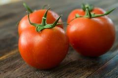 Tomates maduros jugosos en una tabla de madera Fotografía de archivo