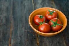 Tomates maduros jugosos en una tabla de madera Fotos de archivo