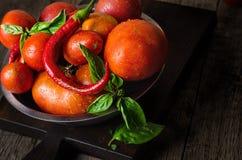 Tomates maduros rojos con pimientas y albahaca Fotografía de archivo