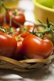 Tomates maduros rojos en la vid en una cesta Imágenes de archivo libres de regalías