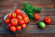 Tomates maduros, rojos en una taza y un tomate verde Foto de archivo libre de regalías
