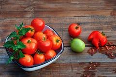 Tomates maduros, rojos en una taza y un tomate verde Fotos de archivo libres de regalías