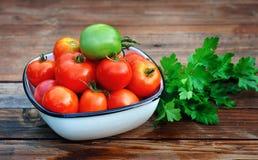 Tomates maduros, rojos en una taza y un tomate verde Imágenes de archivo libres de regalías