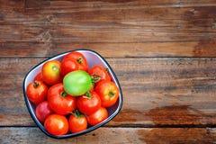 Tomates maduros, rojos en una taza y un tomate verde Fotografía de archivo libre de regalías