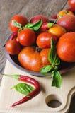 Tomates maduros vermelhos com pimentas e manjericão Imagens de Stock Royalty Free