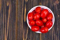 Tomates maduros vermelhos pequenos na bacia na tabela de madeira, vista superior Imagens de Stock