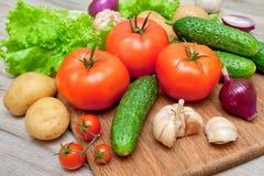 Tomates maduros y otras verduras en una tabla de cortar Fotos de archivo