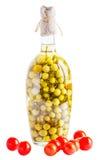 Tomates maduros y tomates adobados en una botella en una parte posterior del blanco Imágenes de archivo libres de regalías