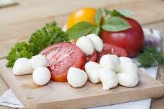 Tomates, manjericão e mozzarella cortados em uma placa de madeira Fotografia de Stock Royalty Free