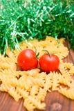 Tomates, massa e ouropel no fundo de madeira Imagens de Stock Royalty Free