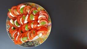 Tomates, mussarela e manjericão em um potenciômetro Escuro - fundo cinzento Fotografia de Stock Royalty Free