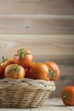 Tomates na cesta na tabela de madeira Imagem de Stock