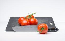 Tomates na placa de corte Imagens de Stock