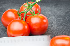 Tomates na placa de corte com faca fotos de stock royalty free