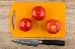 Tomates na placa de corte e na faca de cozinha na tabela Foto de Stock