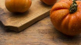 Tomates na placa de desbastamento de madeira Foto de Stock Royalty Free