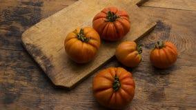 Tomates na placa de desbastamento de madeira Foto de Stock