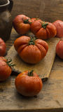 Tomates na placa de desbastamento de madeira rústica e na tabela de madeira Foto de Stock