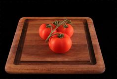 Tomates na placa de corte Imagem de Stock Royalty Free