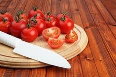 Tomates na placa de estaca de madeira que está sendo cortada ao meio pela faca branca Fotos de Stock