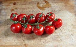Tomates na placa de madeira fotos de stock