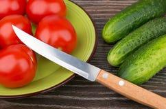 Tomates na placa de vidro verde e nos pepinos na tabela Fotografia de Stock Royalty Free