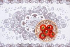 Tomates na tabela e postos lhe em uma cesta Fotografia de Stock Royalty Free